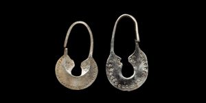 "Viking Silver Lunulate Earring Pair. 10th-12th century AD  A group of two earrings, each with a round-section loop and carinated lunulate plaque; a series of punched pellets to the outer edge and a similar triangle at the base of each end of the loop, Baltic workmanship. 5.25 grams total, 36-40mm (1 1/2"")"
