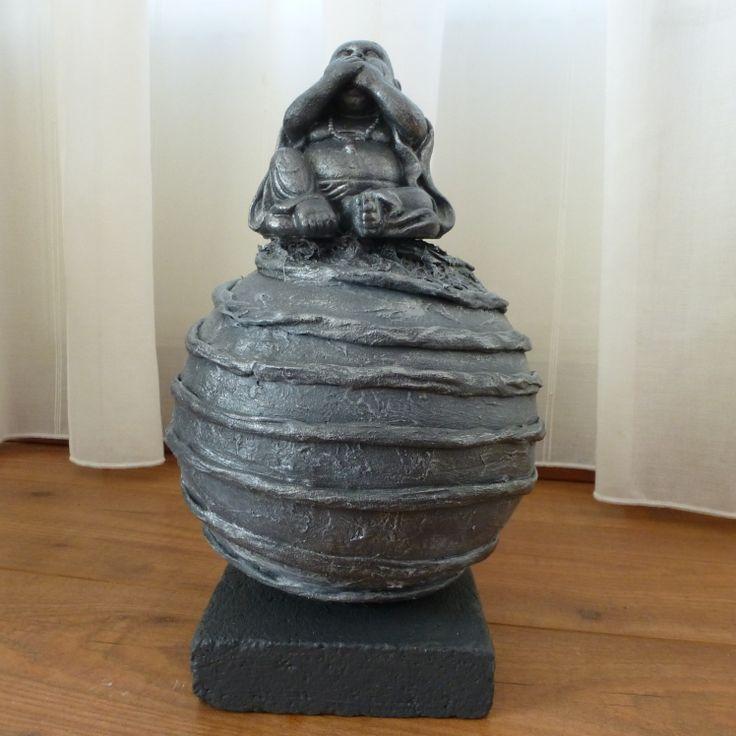 Decoratie beeld of figuur van een Boeddha zwijgen geplaatst op een bol. De bol is bewerkt met ringen. Meestal wordt een Boeddha cadeau gegeven aan goede vrienden of kennissen. Als: Verjaardag-Relatie-Huwelijks-Jubileum-Vriendschap-Afscheid cadeau en of geschenk. Jezelf een Boeddha Cadeau doen kan natuurlijk ook. Het is een mooie decoratie voor in huis. Het verhaal dat dit ongeluk zou brengen is een westers fabeltje.