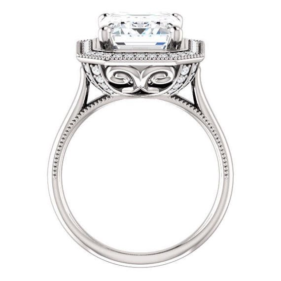 This spectacular engagement ring features a stunning 11x9mm emerald-cut Supernova Moissanite surrounded by a halo of sparkling round diamonds with milgrain borders atop a plain band. The undergallery features a unique filigree work with diamond accents for a wonderful surprise. If