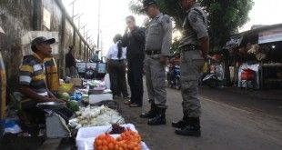 Petugas Satpol PP saat mengingatkan PKL dibelakang PT Eratex Djaja