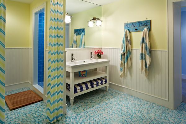 Colorful bathroom design with beadboard paneled lower walls and yellow wall color. The bathroom features a white washstand with shelves, featuring a trough sink with double faucets. A large frameless mirror hangs over the washstand with inset polished nickel sconces. A rustic blue towel hook holds a pair of yellow and blue towels beside the sink. To the left of the sink is the opening to the blue tiled walk-in shower. The opening is flanked by a pair of blue, yellow and white chevron drapes.