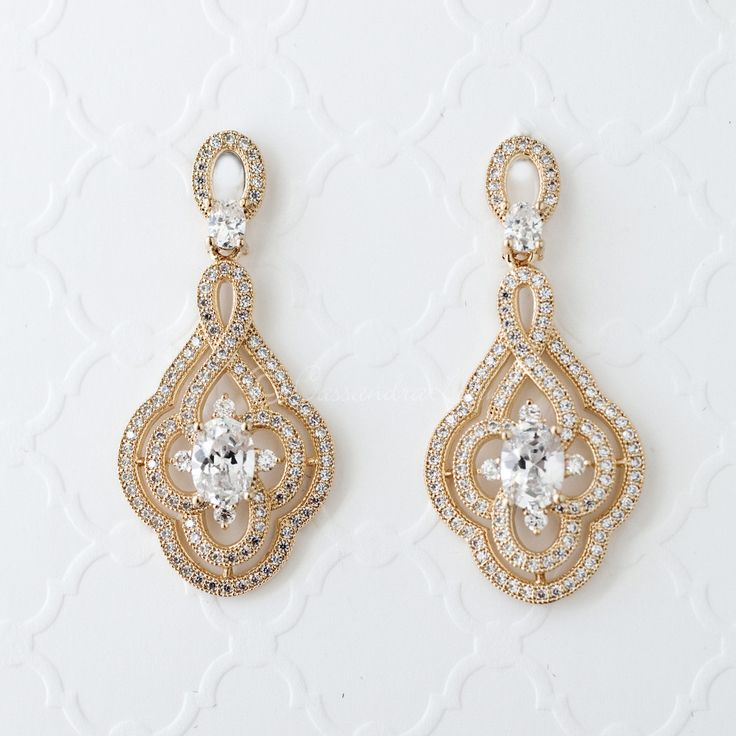 These eye-catching art deco earrings are set with gorgeous cubic zirconia and feature a whimsical swirl design with a center oval stone. These dazzling earrings are the perfect mix of modern and vintage for any formal affair.