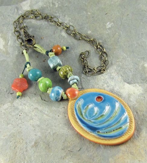 This ocean themed necklace is perfect for the woman who loves the roar of the surf and the sand between her toes. It features a striking, handmade ocean wave pendant with matching handmade ceramic beads, which are knotted on green leather lace.The amazing handmade ocean wave pendant depicts abstract waves with a setting sun. This ocean scene is mounted on a background of natural golden brown clay that has been textured with a cross-hatch pattern.