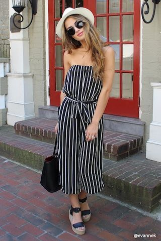 A crinkled woven strapless jumpsuit featuring an elasticized bust, a striped pattern, wide-leg design, a belted waist, and front slip pockets.