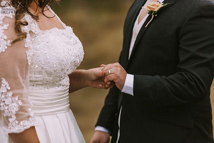 Winter wedding ceremony in Queenstown, New Zealand. Bride and groom exchange rings.
