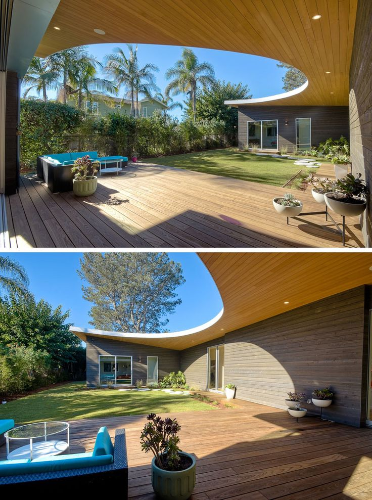 Looking out on this modern wood patio, a curved roof with hidden lighting is revealed. Bright blue patio furniture provides a nice place to lounge outside.
