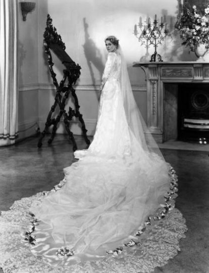 1933: Actress Ann Todd models her wedding gown. Designed and made by Helene Galin it is of white and silver damask satin with a cloud pattern. A long train is edged with lace belonging to her great great grandmother.