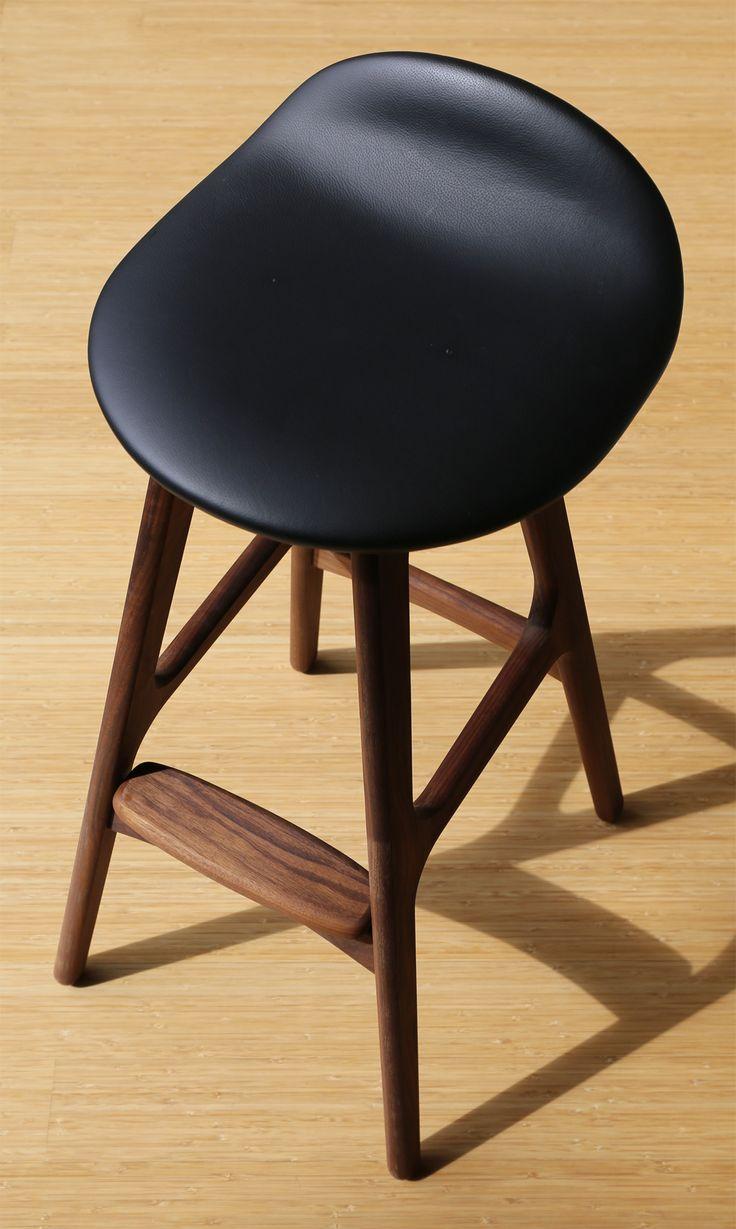 Timeless Erik Buch Model 61 bar stool in walnut & black leather on a sunny day.