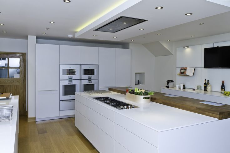 The tall run houses a Gaggenau Vario larder fridge, two Gaggenau ovens, a combination steam oven, a microwave oven and two deep warming drawers. This combination gives the client unparalleled control and usability in the kitchen for all possible cookery needs. The flush fitting ceiling extractor is housed in its own bespoke surround that includes recessed LED lighting. Kitchen by bulthaup Winchester.