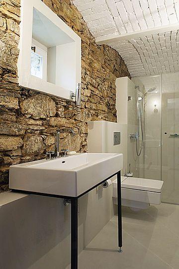 V koupelně v bývalém výminku architekti ponechali původní cihelnou klenbu a sladili ji s celkovým konceptem, založeným na kontrastu bílých ploch a kamenného zdiva.