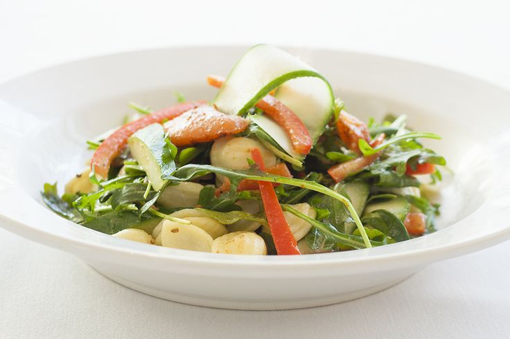 Smoked salmon pasta salad with cucumbers, red onion, red bell pepper, and arugula in a lemon caper vinaigrette