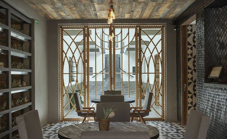 Rustic wood plank ceiling and Art Deco glass doors adorned with ornate brass ornamentation | Asta Boutique Interiors.
