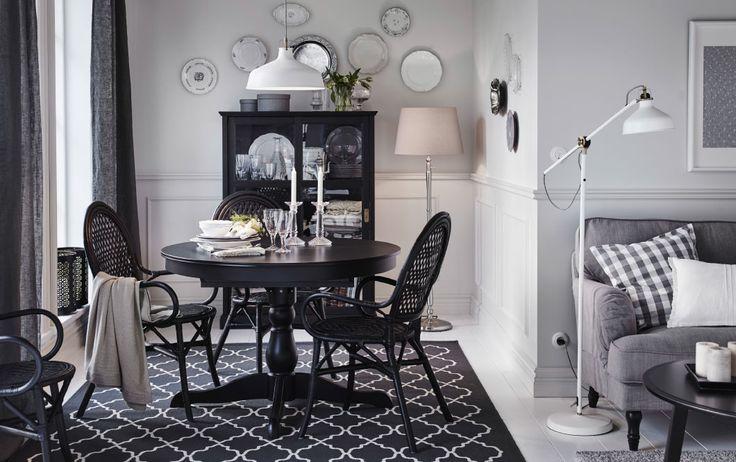 Une salle à manger de taille moyenne avec une table ronde noire et quatre chaises en rotin. Une vitrine, noire également, complète l'ensemble.