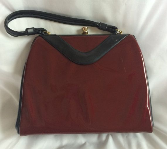 Vintage mid-century maroon patent leather purse with black leather accents and handle.
