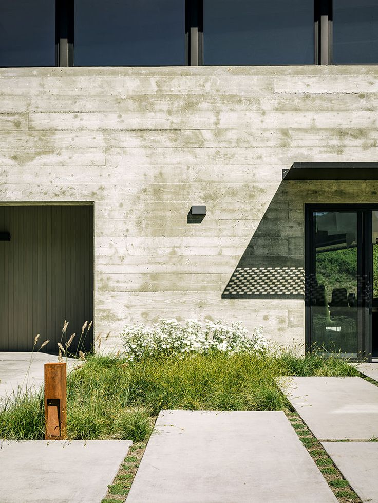 Concrete pavers in the entrance to the garden of a modern eco-conscious pavilion in California by Feldman Architecture with Bernard Trainor landscape design.