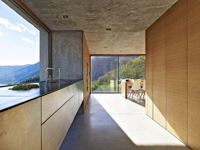 Kuchyň se nachází v nejvyšším přístupovém podlaží. Je řešena velmi minimalisticky a je zřejmé, že nejvýraznějším aspektem prostoru je ničím nerušený výhled od pracovní plochy, zabírající celou šířku stěny a vyvolávací dojem tělesa vznášejícího se nad hladinou jezera