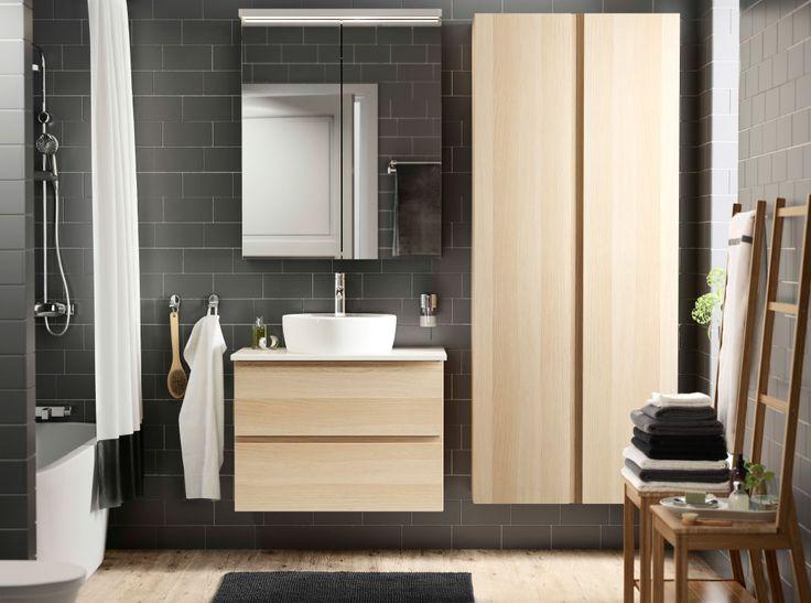 Salle de bains carrelée de gris-brun, avec meuble lavabo et armoire effet chêne blanchi. Un lavabo blanc et un élément mural à portes miroir complètent l'ensemble.