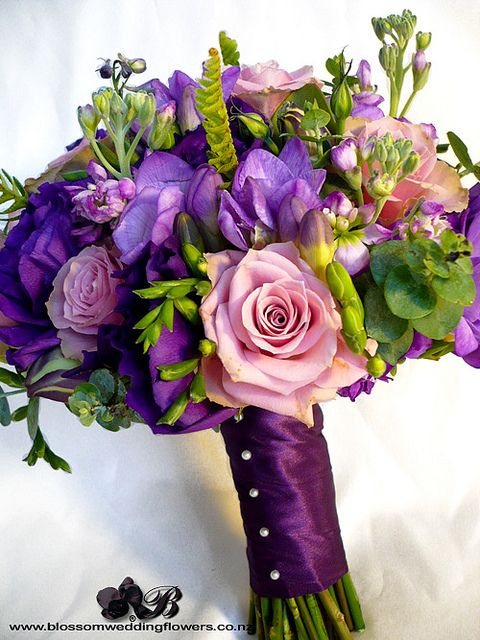 """Bride's bouquet of purple lisianthus, purple stock, purple delphinium, purple freesia, dusky purple and coffee """"old dutch"""" roses, with touches of ladder fern, eucalyptus and berries, bound in deep purple satin."""
