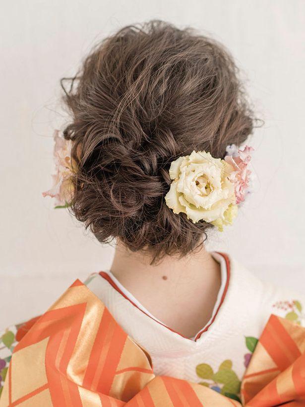 トルコキキョウは、両側の耳の後ろにアシンメトリーに配して奥行き感とニュアンスを出します。白い小花をつけるズイナを垂れ下がるようにあしらって、...