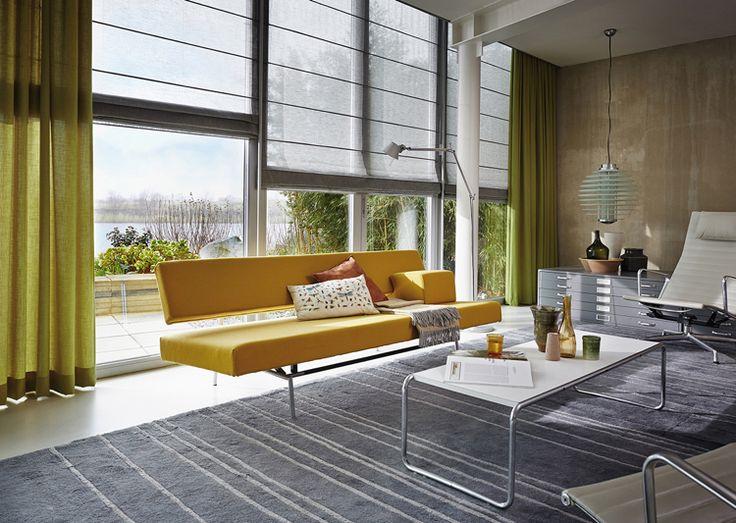 salon contemporain aménagé avec des stores bateau gris et des rideaux occultants vert pistache