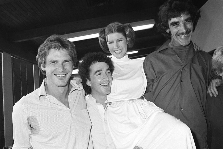 """Actor Harrison Ford, left, who played Han Solo in the move """"Star Wars,"""" is pictured with his co-stars, Anthony Daniels, who played C-3P0; Carrie Fisher who played Princess Leia, and Peter Mayhew who played Chewbacca the Wookiee, as they take a break from filming a television special to be telecast during the holidays, Oct. 5, 1978."""