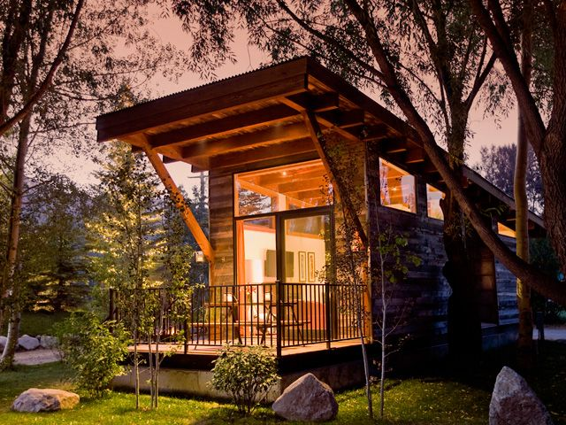 At first glance, the 400-square-foot Wedge, designed by Wheelhaus, appears to be a tiny luxury cabin but it's actually a mobile Park Model RV. Lofty 17-foot ceilings and a large sliding glass window at the front give an open feel to the rustic yet modern dwelling, which features a bedroom, bathroom, and combined kitchen/living room area. A 100-square-foot deck offers additional entertaining space.    - CountryLiving.com