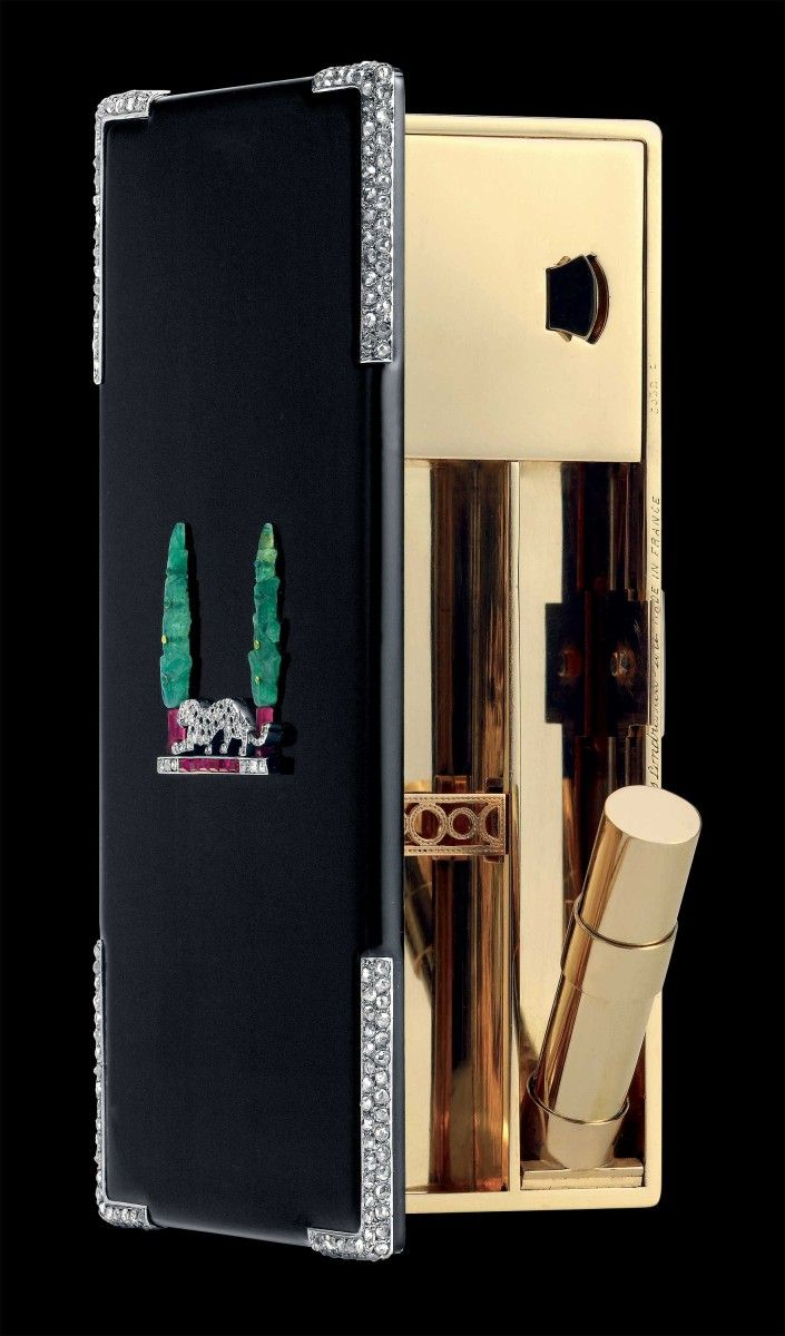 Panther Vanity Case, Cartier Paris, 1928. Yellow gold, platinum, black enamel, rose- and baguette-cut diamonds, engraved emeralds and green enamel (cypress), two square-cut emeralds, rubies (trunk), calibrated and faceted rubies (earth) and onyx cabochons (panther). The interior fitted with a mirror, a lipstick, a covered powder compartment, and a cigarette compartment with gold openwork retaining clip.