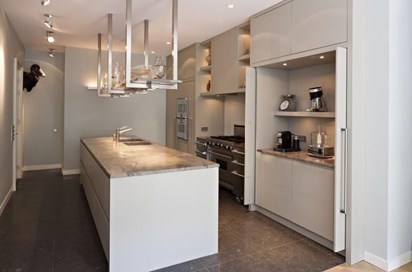 Mooi hoe er een werkruimte verwerkt zit achter een kastenwand. The Living Kitchen B.V. by Paul van de Kooi