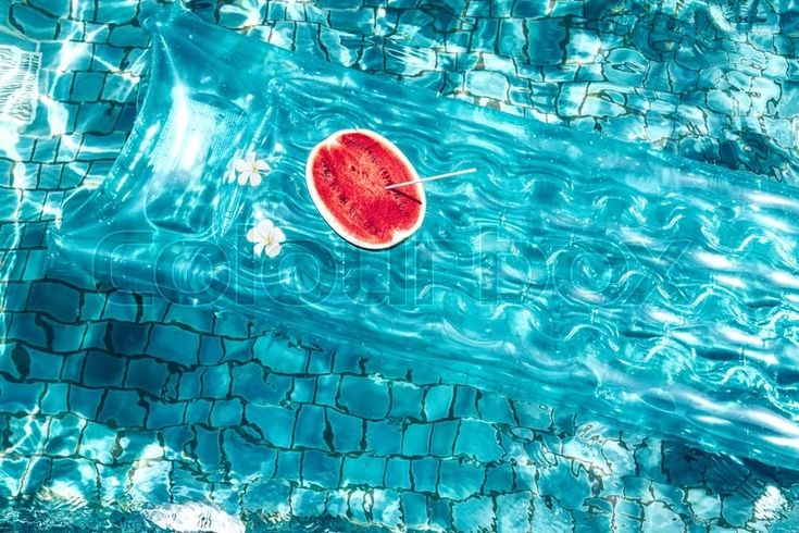 Stock image of 'Watermelon on floating mattress in the blue pool. Tropical fruit diet. Summer holiday idyllic.'