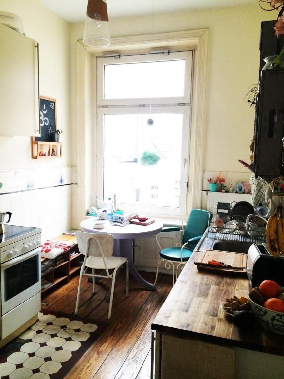 Wunderschöne gemütliche WG-Küche in Hamburg Neustadt mit großem Fenster, türkisem Stuhl und hölzerner Anrichte sowie Dielenboden. Wohnen in Hamburg. #Hamburg #WohneninHamburg #Küche #Einrichtung #Esstisch #Essbereich #kitchen #interior #design #diningtable