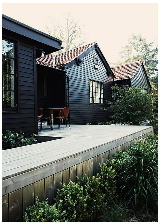 Black clapboard, weathered wood deck in a clean design