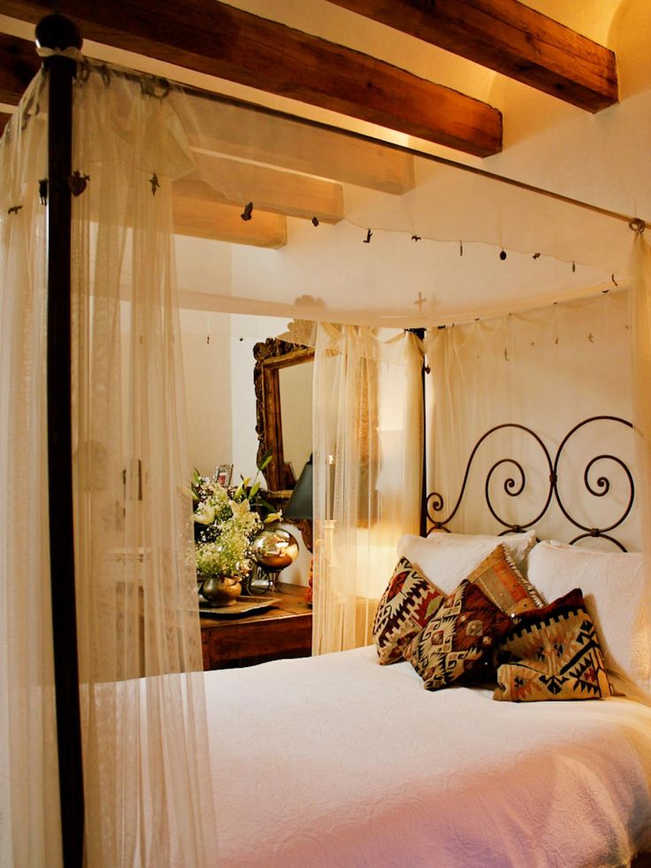 A heavily beamed ceiling highlights this guest bedroom with an iron canopy bed. Light colored linens are offset by colorful patterned pillows and a sheer bed curtain provides a measure of privacy.