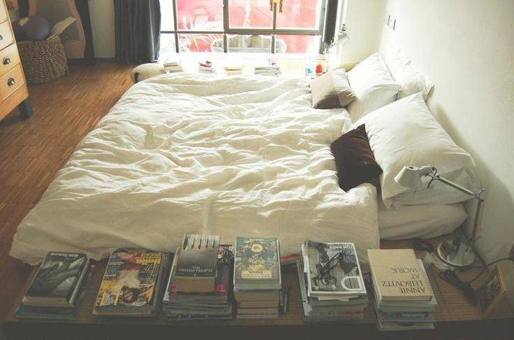 Bed on floor with books and laid back decor