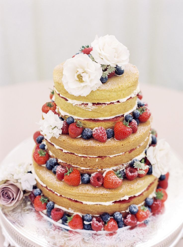 Fragole e frutti di bosco per accompagnare una torta a piani in pan di spagna e panna fresca
