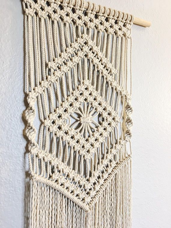 This macrame wall hanging is handmade with 1/8 organic cotton rope with 18 x 5/8 wooden dowel. The wall hanging measures 18 across and approx. 38 down. This small macrame wall hanging is the perfect way to add some texture to any wall! Hang it as a single piece of art or part of an