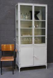 Witte ijzeren apothekerskast met glas aan drie zijdes. De kast heeft vier houten legplanken (één achter de dichte deuren).