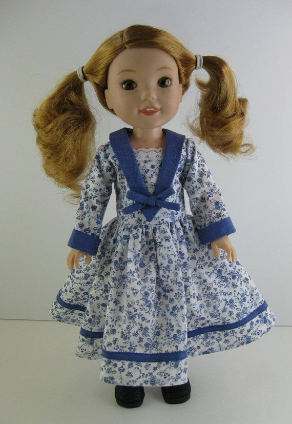 Your Wellie Wisher will look beautiful in this sweet dress and shoes.  The long sleeved dress is made from a blue and white floral print. The cuffs, collar, and bow are made from blue fabric. A bit of white lace is used to trim the bodice neckline, and a blue bias strip is sewn near the hem of the skirt. The back of the dress closes with velcro.  Sparkly black shoes will slip onto your Wellie Wishers feet.   Doll Not Included  Made in a smoke free home.