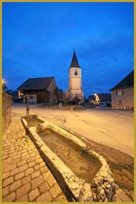Photo à la tombée de la nuit au-dessus de l'abreuvoir à bestiaux, face à l'église Saint-Georges des XIIe et XVIIIe siècles, dans la rue Principale de Franken. Photos de Franken, visiter le Sundgau, tourisme en Alsace.