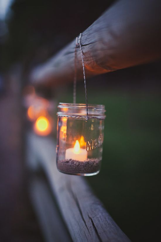 Add warm rustic appeal to your outdoor wedding by hanging candles in mason jars when the sun goes down.    Photo courtesy Ameris Photography.