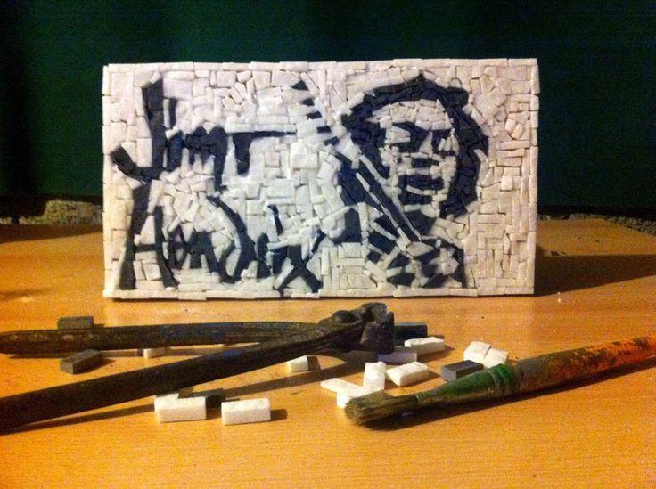 """La nostra creazione più recente viene dedicata al più grande chitarrista rock, Jimi Hendrix. Una placchetta che lo raffigura in modalità """"stencil"""" insieme alla sua Fender Stratocaster. La placchetta è decorata in marmo di Pietrasanta con 31 centimetri di lunghezza e 17 di larghezza. Ovviamente, sarà accompagnata dal Certificato di Autenticità."""