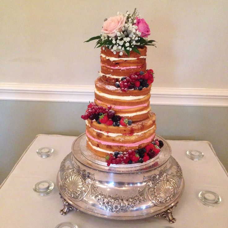 3 tier naked cake lightly dressed with berries and fresh flowers. Each tier has 1 layer filled with pink buttercream. www.kellylou.com