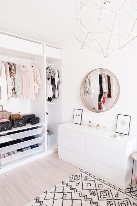 white minimalistic bedroom with circle mirror and open closet