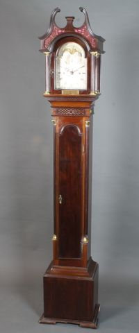 "An early 20th Century mahogany longcase clock of diminutive  size in the mid 18th Century style, having an 8"" broken arch  silvered Roman dial with moon phase decorated maritime scene  and chateau, set 8 day movement, chiming gong. The case with  moulded broken swan neck pediment above a blind fret cut frieze  and fluted column supports, the trunk with arched top door  flanked by fluted quarter pilasters, raised on a box base with  block feet, bears inscribed brass plaque  SOLD FOR £1200"