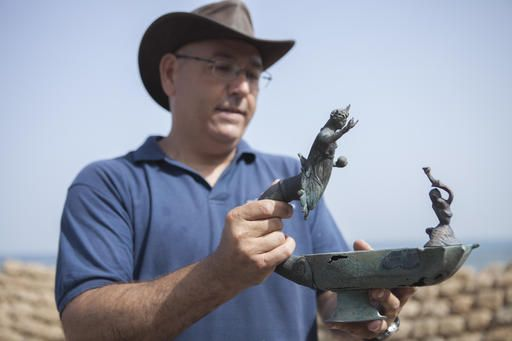 Jacob Sharvit, director of the Marine Archaeology Unit of the Israel Antiquities Authority, holds a bronze lamp depicting the image of a Roman sun god Sol Invictus, in Cesarea, Israel, Monday, May 16, 2016. Israeli archeologists say two divers have made the country's biggest discovery of Roman-era artifacts in three decades. (AP Photo/Dan Balilty)