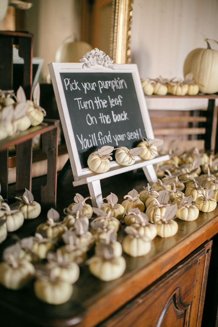 """Escort cards at this fall wedding were attached to seasonal mini white pumpkins as """"leaves."""""""