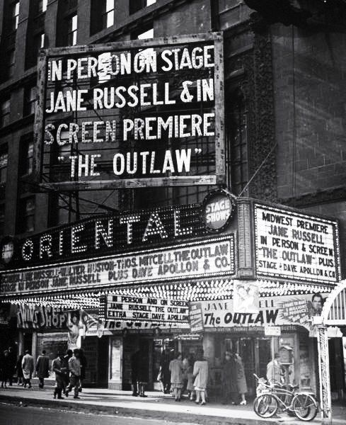 """A theater marquee advertising the movie """"The Outlaw."""" Photograph by Wallace Kirkland. New York City, 1946.:"""