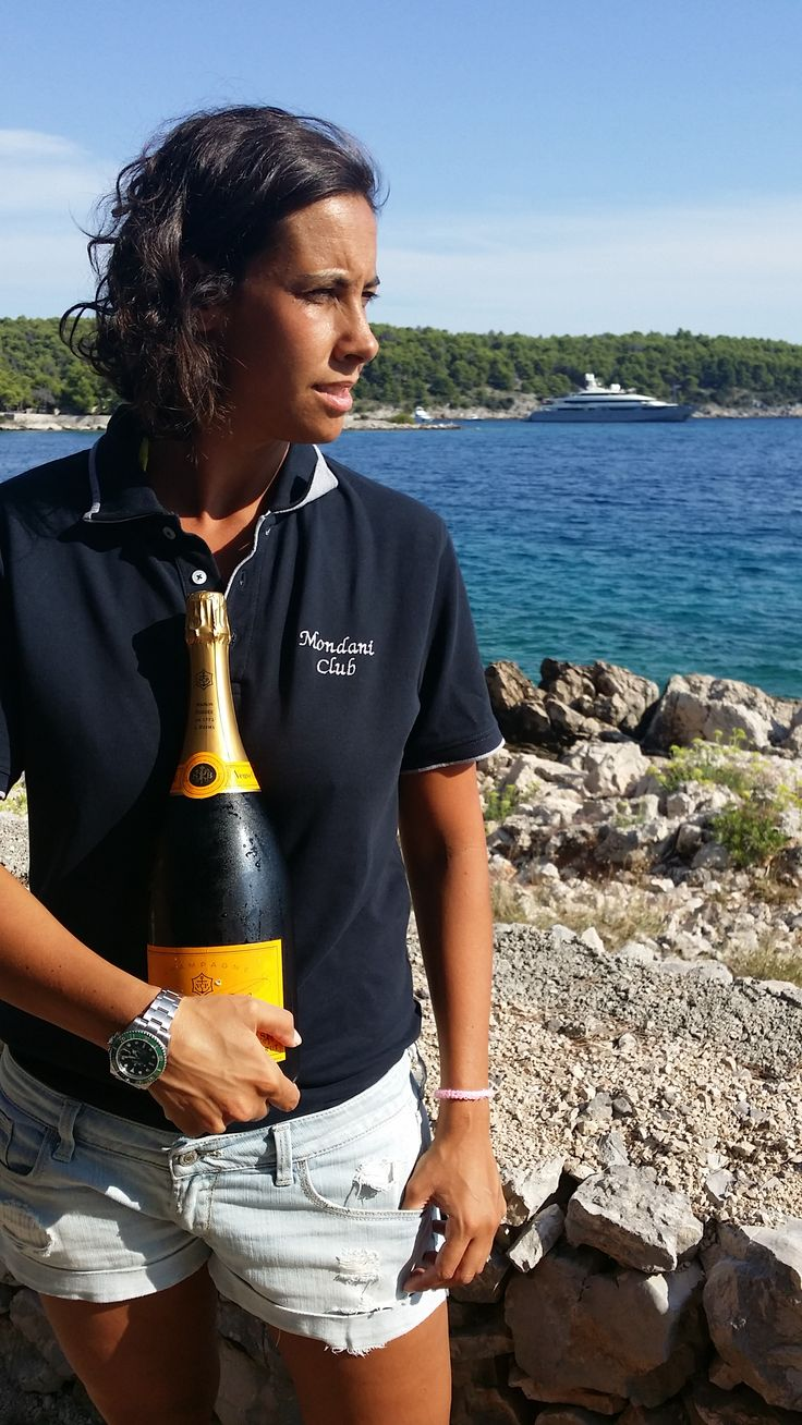Giorgia Mondani with the Mondani Club tshirt, a Rolex Submariner ref 116610 and a Veuvue Clicquot magnum bottle
