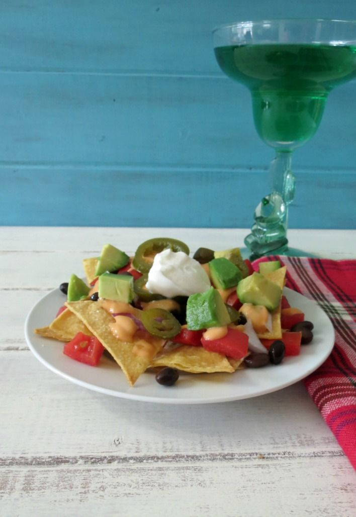 Low Calorie Nachos -  A traditional Mexican side dish made with homemade tortilla chips and topped with cheese, black beans, tomatoes and onions.