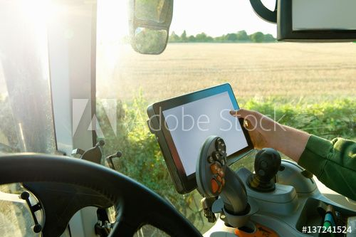 Farmer's hand driving tractor using touchscreen on global positioning system