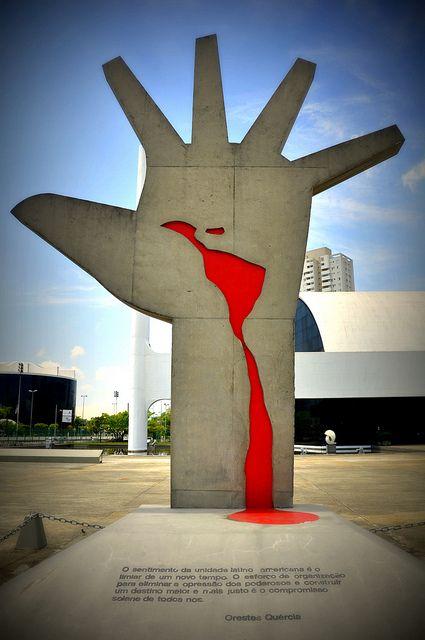La Mano,(escultura de Oscar Niemeyer), en cuya palma se nota el mapa de Latinoamerica hecho con tinta roja, en referencia a la sangre derramada durante siglos de dominación y opresión de la región. Se trata de un emblema de este continente colonizado brutalmente y aún hoy en su lucha por la identidad y la autonomía cultural, política y socio-económica.  Ciudad de São Paulo